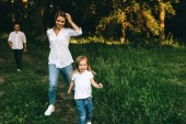 selective focus of family having fun together in forest on summer day