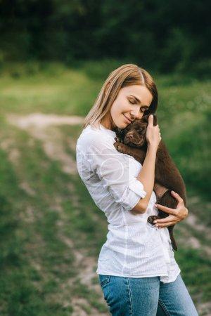 Photo pour Vue latérale de jeune femme souriante étreignant chiot labrador mignon dans les mains - image libre de droit