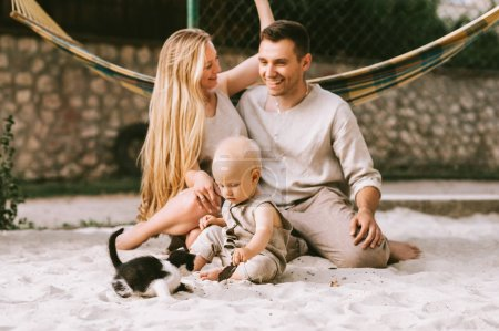 happy family with little son and kitten sitting on sand at countryside
