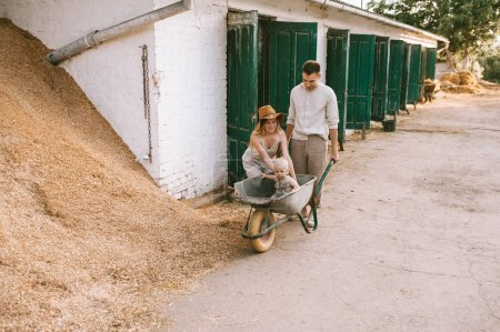 Photo for Parents and little son in wheelbarrow at countryside on summer day - Royalty Free Image