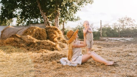 woman in hat and cute little boy in linen clothing resting on hay at countryside