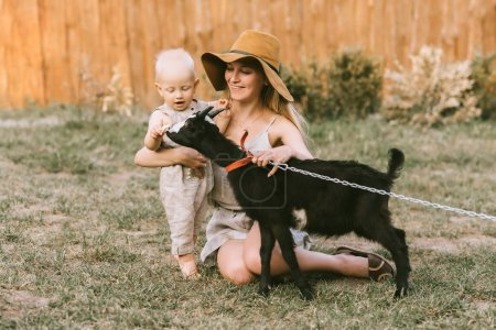 smiling mother in hat and little son petting domestic goat on green grass at countryside
