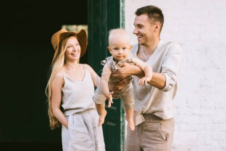 portrait of happy parents with cute little son in village