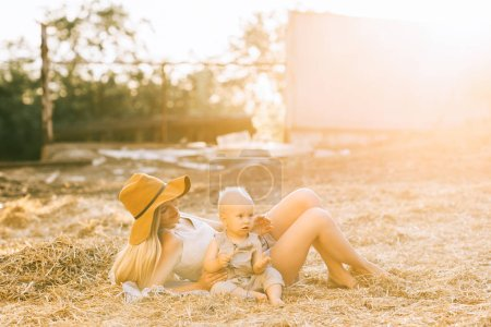 mother and cute little boy in linen clothing resting on hay at countryside