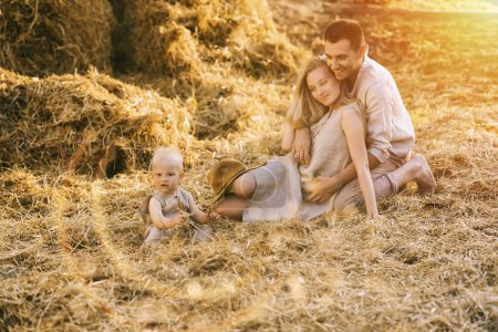 parents and little son in linen clothing resting on hay at countryside