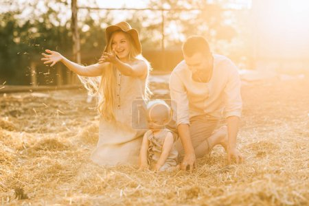 happy parents and little son in linen clothing resting on hay at countryside
