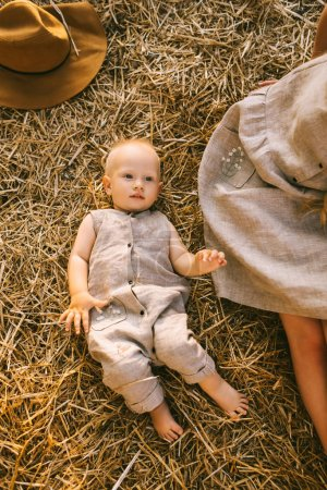overhead view of mother and son in linen clothing resting on hay together