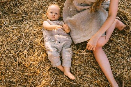 vue aérienne de la mère et le fils dans les vêtements de lin reposant sur foin ensemble