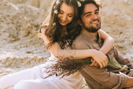 Photo pour Belle fille avec des fleurs dans les cheveux embrassant son petit ami heureux - image libre de droit