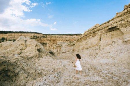 vue arrière du jeune fille en robe blanche, marcher dans le sable canyon avec un ciel bleu