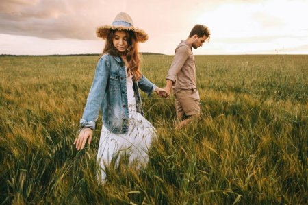 stylish couple holding hands and walking on green meadow