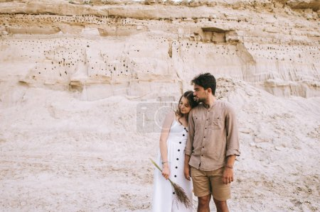 young attractive girl in white dress holding floral bouquet and hugging boyfriend in sand canyon