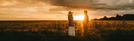 Photo pour Couple élégant tenant la main sur la prairie au beau coucher de soleil avec contre-jour, histoire d'amour - image libre de droit