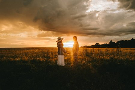 Photo for Young couple holding hands on meadow at sunset with backlit, love story - Royalty Free Image