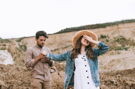 stylish girl closing eyes and holding hands with happy boyfriend in sand canyon
