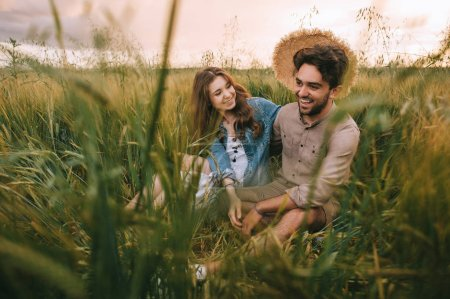 happy stylish couple with straw hat sitting in green grass on meadow