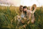 beautiful stylish couple hugging in green grass on meadow