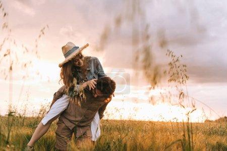 Foto de Hombre feliz piggybacking su novia en Prado de verano - Imagen libre de derechos