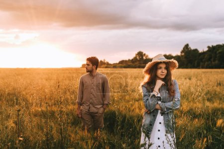 stylish girlfriend in straw hat posing with boyfriend on summer meadow at sunset with backlit