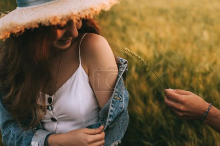attractive smiling girl in straw hat sitting on meadow, while boyfriend touching with wheat ear to her shoulder