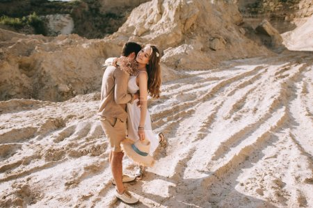 stylish boyfriend embracing and kissing his beautiful girlfriend in sand canyon