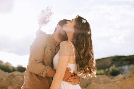 Photo pour Copain embrassant et embrassant sa petite amie avec bouquet floral, avec contre-jour - image libre de droit
