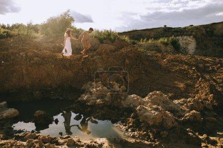 Foto de Elegante pareja cogidos de la mano y caminar sobre las rocas cerca de Charco con reflexión - Imagen libre de derechos