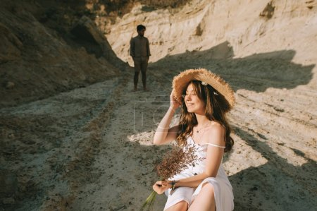 happy young woman in straw hat with floral bouquet sitting in sand canyon with boyfriend behind