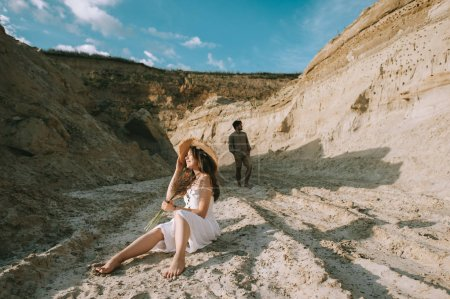 Photo for Happy girl with floral bouquet sitting in sand canyon with boyfriend behind - Royalty Free Image