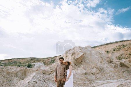 Photo pour Couple main dans la main et, debout dans le sable canyon avec cludy ciel - image libre de droit