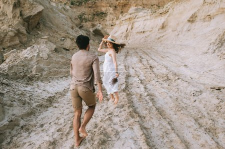 beautiful happy couple running in sand canyon, love story