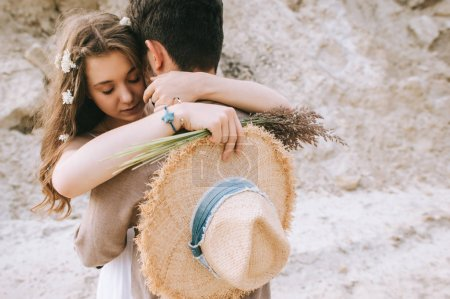 attractive girl with flowers in hair hugging her boyfriend while holding floral bouquet and straw hat