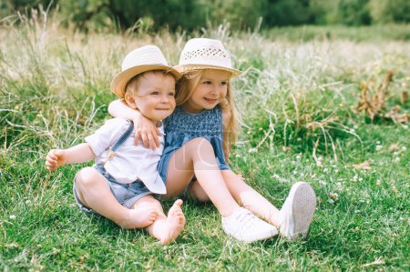 adorable stylish children in straw hats sitting in green field