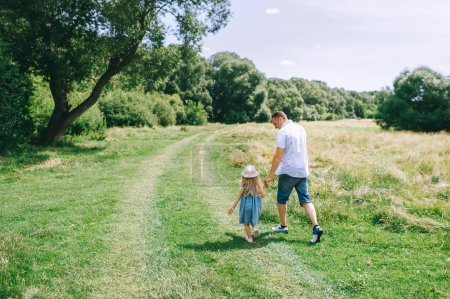 back view of father holding hands with daughter and walking in field