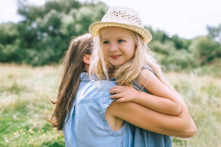 mom hugging with daughter in summer field