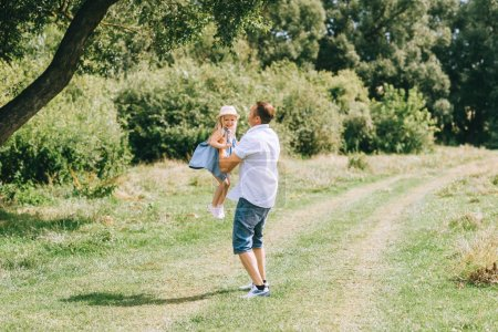 father playing with stylish adorable daughter
