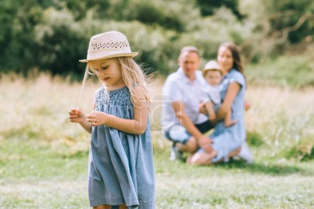 Photo for Little girl in straw hat in summer feild with family behind - Royalty Free Image