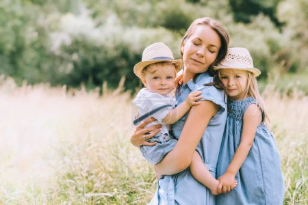 beautiful mother hugging with two kids in field