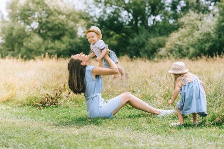 beautiful stylish mother playing with children in field