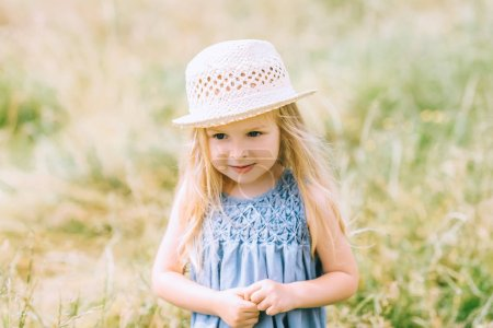 Photo for Adorable blonde child in dress and straw hat - Royalty Free Image