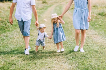 Photo for Family with two kids holding hands and walking on summer feild - Royalty Free Image