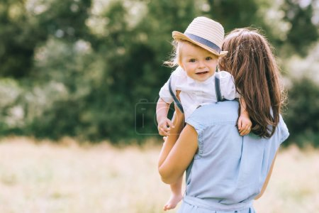 stylish mother holding baby boy on hands and walking in field