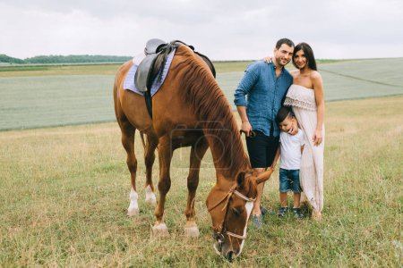 smiling parents and son standing on field with horse