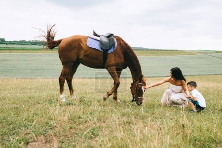 mother and son palming horse on field