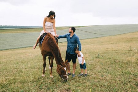 mother riding brown horse, father and son standing on field