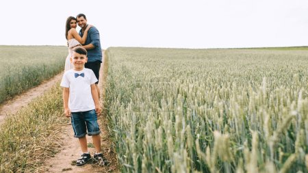 Photo for Parents hugging and son looking at camera on path in field - Royalty Free Image