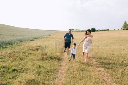 Photo for Parents and son running on path in field - Royalty Free Image