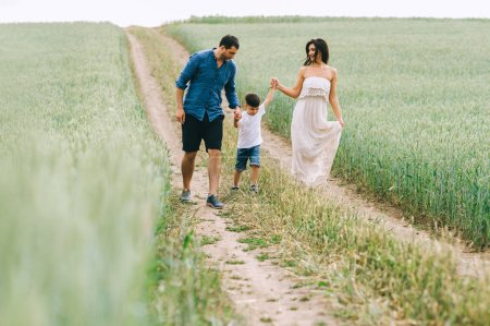 parents and son holding hands and walking on path in green field