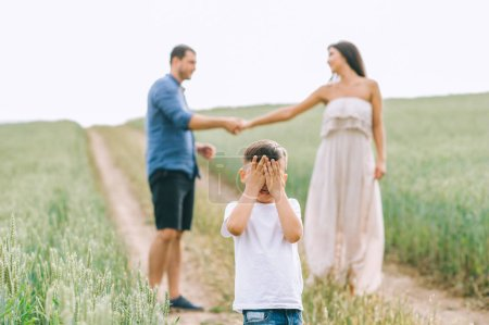 parents holding hands and son covering eyes on path in field