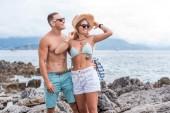 smiling girlfriend and boyfriend looking away at beach in Montenegro